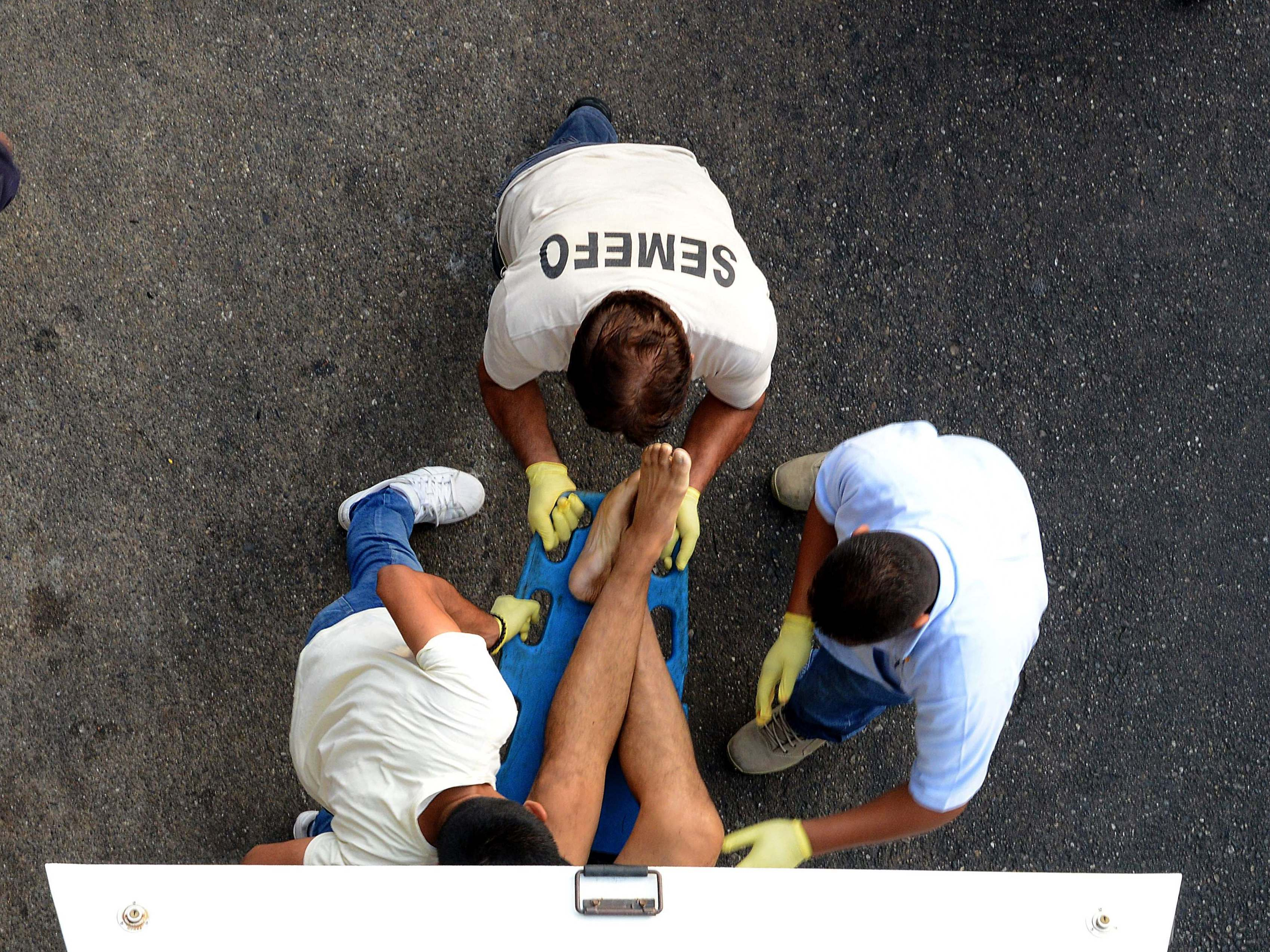 Forensic personnel load the corpse of a man into a van