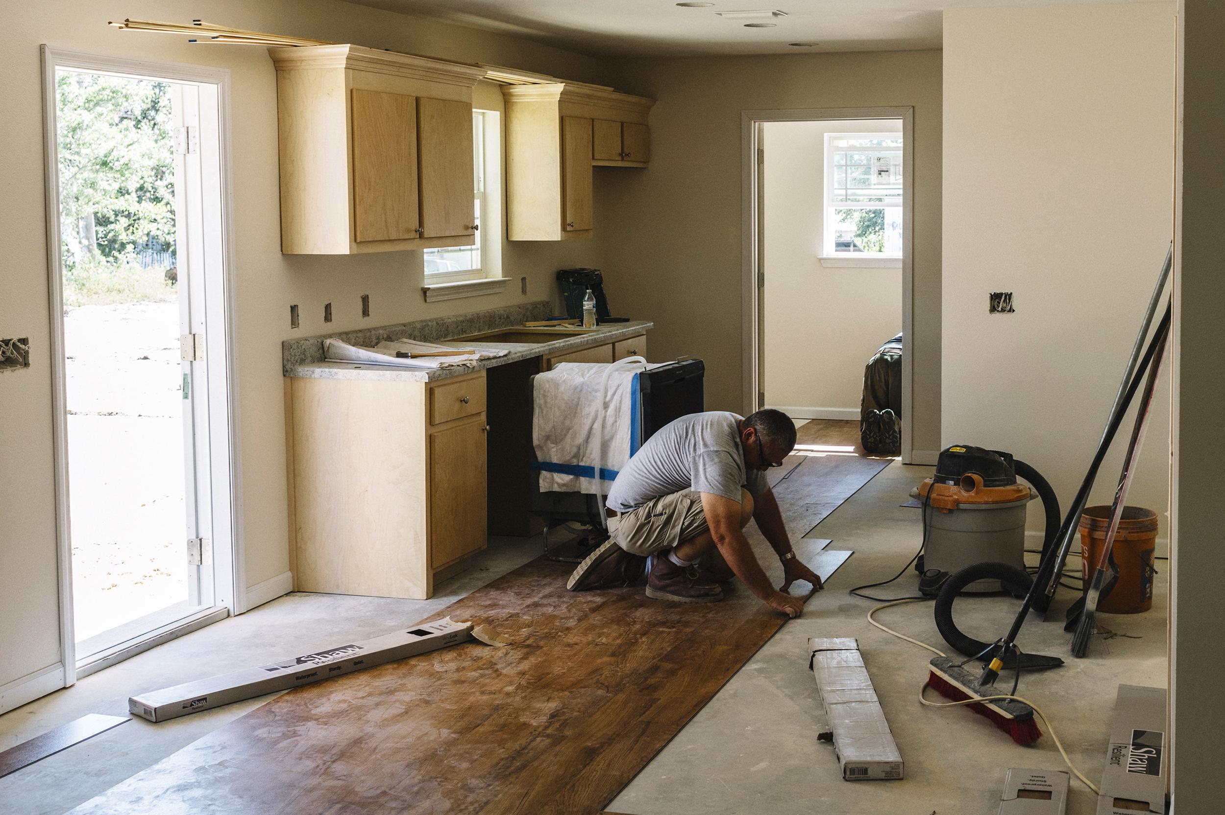 Construction Manager Ross Potts Installs Flooring In A Habitat For